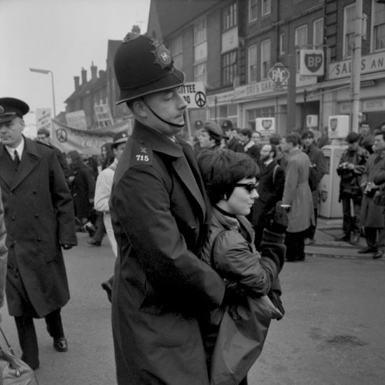 CND demonstration in Ruislip, north-west London. A woman wearing sunglasses and smoking a cigarette is carried away from the demonstration by a police constable