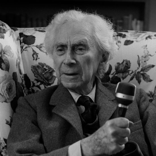 British philosopher, logician, mathematician, historian, writer, social critic, political activist and Nobel laureate Bertrand Russell sits in a chair and holds a microphone whilst looking out of shot