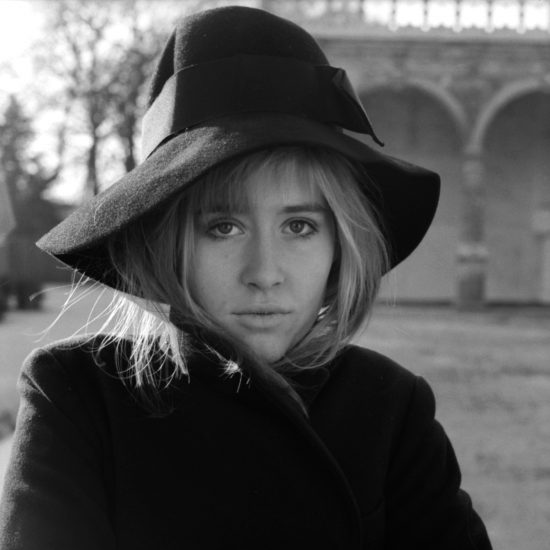 Portrait of British actress Susan Penhaligon in a park, wearing a fashionable hat and wrapping her coat around her, circa December 1964