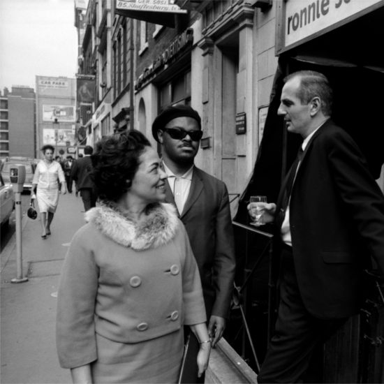 Mrs Edith Kirk smiles at Ronnie Scott as he holds a glass of wine and stands alongside Rahsaan Roland Kirk, outside Ronnie Scotts' Jazz Club, 39 Gerrard Street, London circa 1963