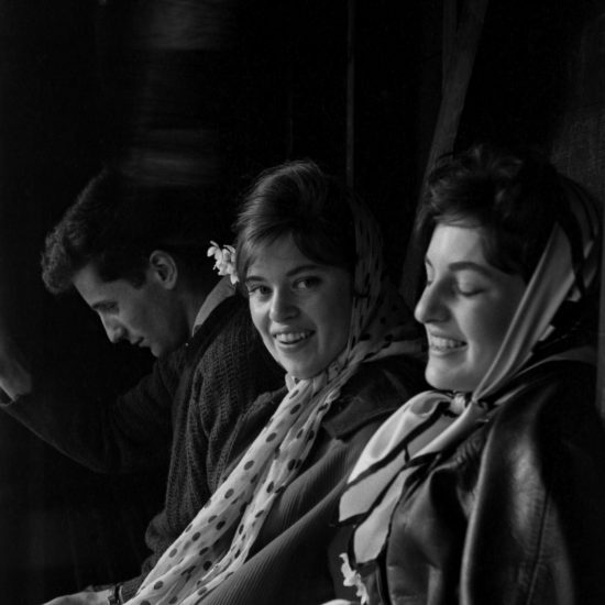 Two women and a man sit in shadows during the Aldermaston to London march in April 1960