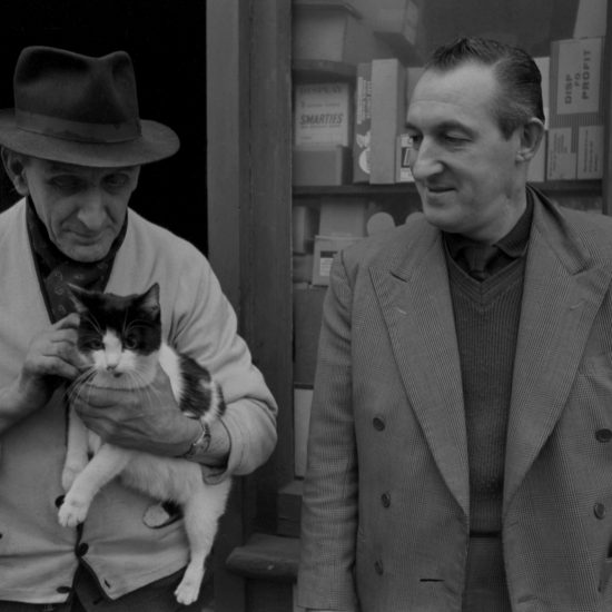 In 1964, an elderly white male (the 'man who did not sleep'), stands outside his general  store in London. The man who did not sleep holds a cat in his arms and is accompanied by a younger male: they both look at the cat