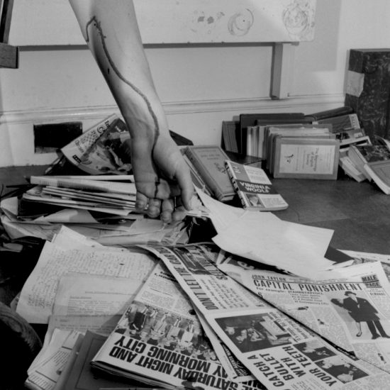 An arm with blood trickling from a vein hangs into the frame: the blood drips onto papers and books on the floor