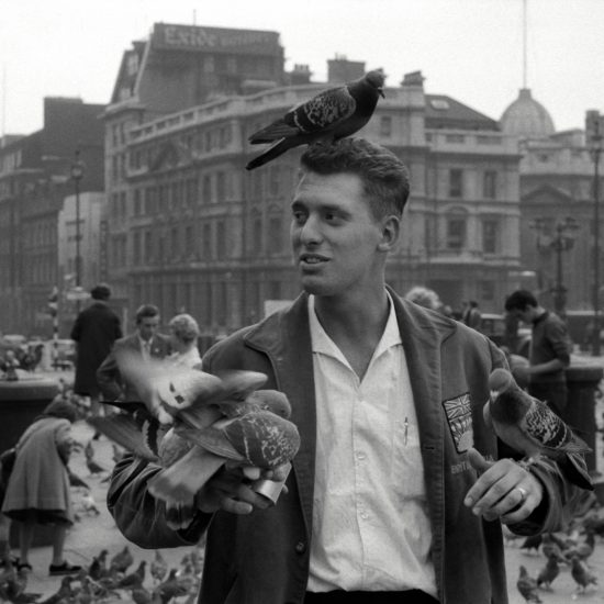 A member of the Canadian Armed Forces in Europe feeds pigeons in Trafalgar Square, London, circa 1961