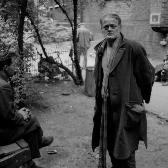 Some homeless men wait outside a soup kitchen venue, possibly a church. One man appears to have a black eye