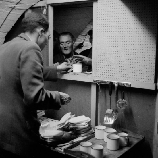 A volunteer worker hands a cup of tea to a homeless man queueing in a soup kitchen. Shot from behind, the volunteer also has a pile of bread and empty mugs in front of him