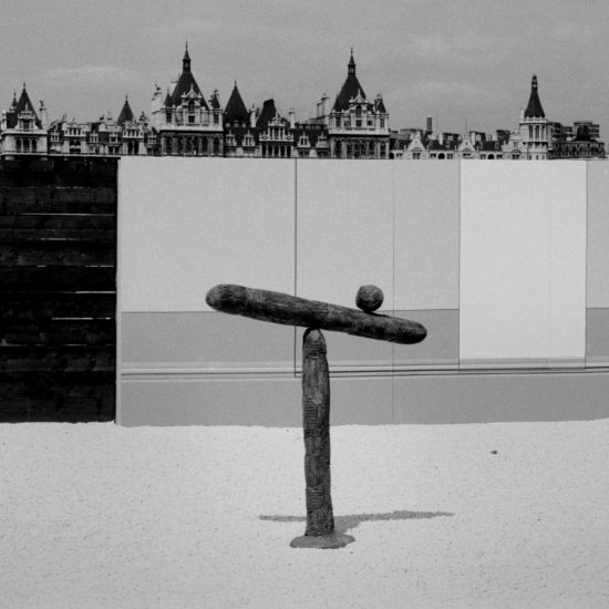 A wooden sculpture in front of a fence, during an exhibition on the Southbank, London, circa 1961