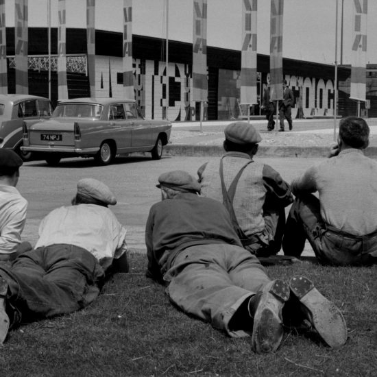 Five workmen relax on the grass and look at a pavilion on the Southbank, London, during a sculpture exhibition, circa 1961