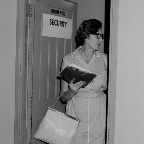 A woman carrying a folder looks off-camera as she emerges from a door marked 'Room no. 19 Security' during the USSR Industrial Exhibition in London, held at Earl's Court,  07-29 July, 1961