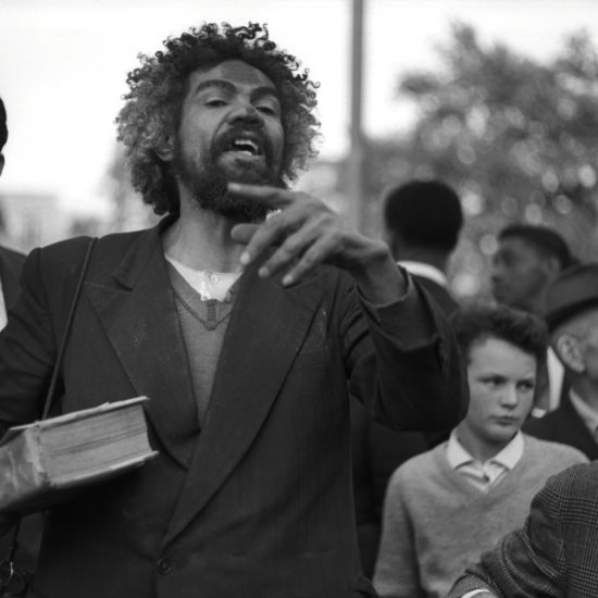A black male with paint on his face and a Bible in his right hand addresses the crowd at Speaker's Corner, Hyde Park, London, circa 1962