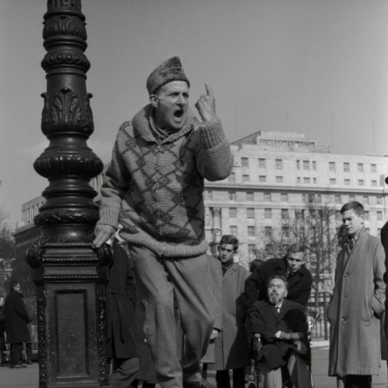 A man in a patterned jumper stands on a soapbox and gestures emphatically at the sky, watched by a small crowd that includes a well-dressed man in a wheelchair. Speaker's Corner, Hyde Park, London, 1964