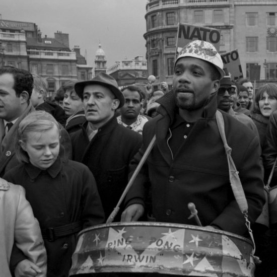 A man playing a steel pan drum with Ping Pong Irwin on the side is surrounded by crowds during the Aldermaston to London march culmination rally in Trafalgar Square, Easter Monday 1964