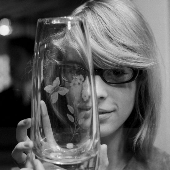 A blonde woman wearing glasses holds an engraved glass vase in front of her face during an exhibition featuring Swedish glassware in London, circa 1961