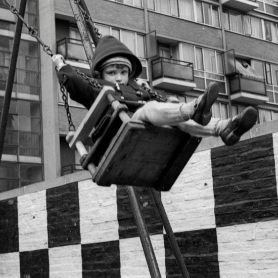 A young girl on a swing flies high in front of a new-build council estate in London