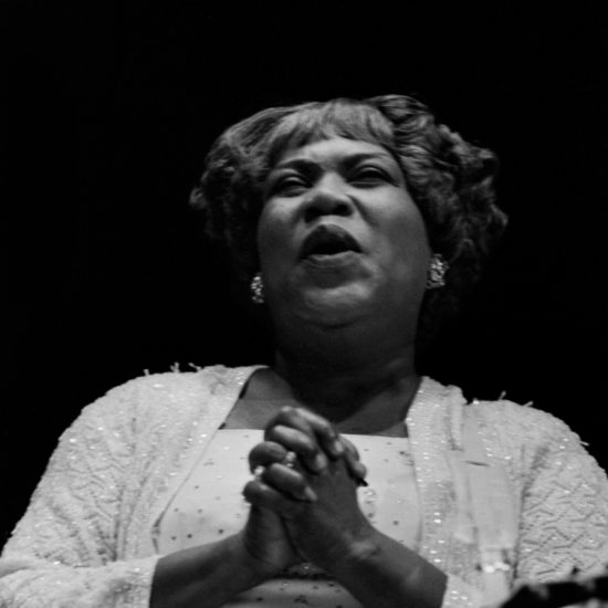 Sister Rosetta Tharpe clasps her hands and smiles whilst on stage at the 1964 Blues and Gospel Caravan, shot as a close up
