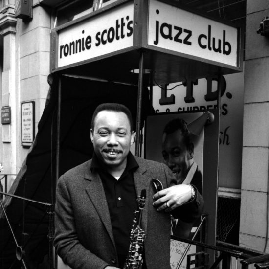 Lucky Thompson holds his saxophone and smiles at the camera outside Ronnie Scott's Jazz Club, Gerrard Street, London, circa 1962