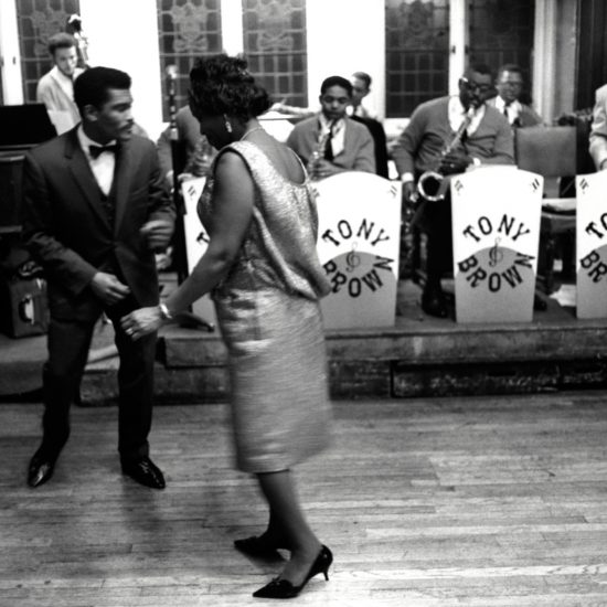 A smartly dressed male and female couple dance in front of the Tony Brown Band after a speech by legendary cricketer Sir Learie Constantine, Trinidad's High Commissioner, at a black cultural event in London, circa 1963-4
