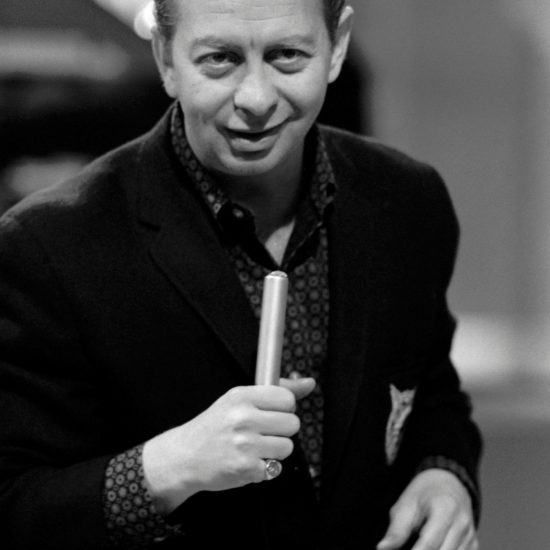 During the filming of BBC-TV Jazz 625 at BBC Television Centre in Shepherds Bush, Mel Tormé holds a microphone in his right hand, shot in close up