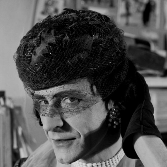 A male transvestite in London's Notting Hill poses for the camera in full drag, including gloves, hat, wig, jewellery, dress and make-up: shot in close-up