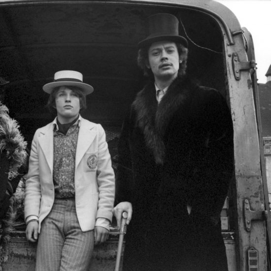People wearing clothes from the boutique Granny Takes A Trip pose in front of a van containing crates of vegetables, by the Salvation Army Church on the Kind's Road, Chelsea, in 1966. L-R: unidentified female in a feather boa, unidentified male in a straw boater, shop founder Nigel Waymouth wearing a top hat