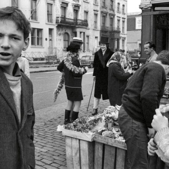 Granny Takes A Trip shop owner Nigel Waymouth and friends wear clothes from the boutique, outside the shop on the Kings Road, Chelsea, in 1966. They stand by a fruit and vegetable stall where shoppers are buying produce and a young man stares at the viewer