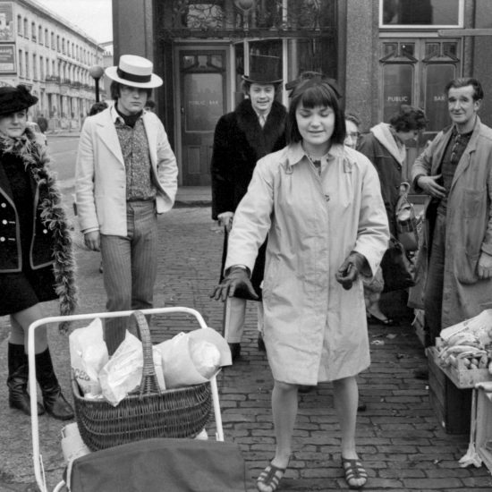 Granny Takes A Trip shop owner Nigel Waymouth and friends wear clothes from the boutique, outside the shop on the Kings Road, Chelsea, in 1966. They stand by a fruit and vegetable stall where shoppers are buying produce and a young woman reaches for a pram in the foreground of the shot