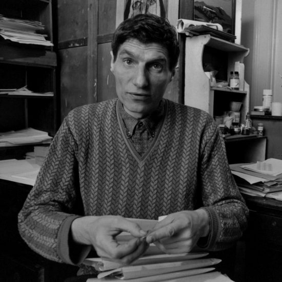 Scottish novelist and author Alexander Trocchi sits at a desk in front of a typewriter in his apartment in London, circa 1964