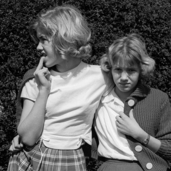 Two young girls, probably sisters, stand in front of a hedge and watch as the 1962 Aldermaston to London March passes through their village. They wear similar clothes and are both wearing the same cardigan at the same time