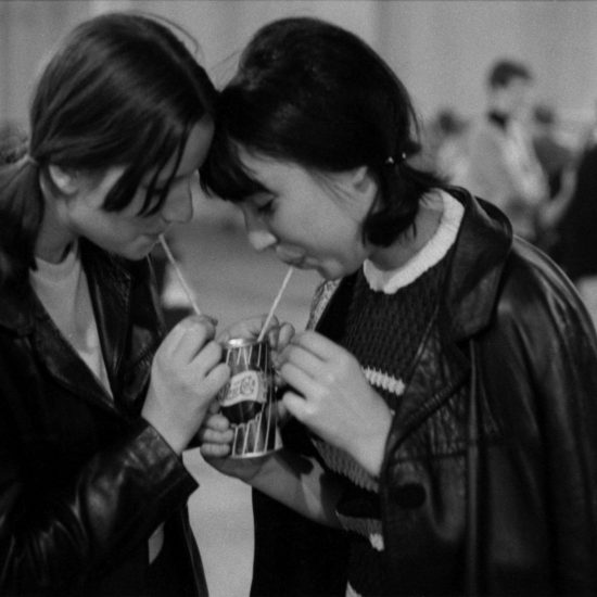 Two young female audience members sip Pepsi Cola through straws during the All Night Rave at Alexandra Palace in London, June 26, 1964. They both have their hair in bunches and are wearing back leather coats