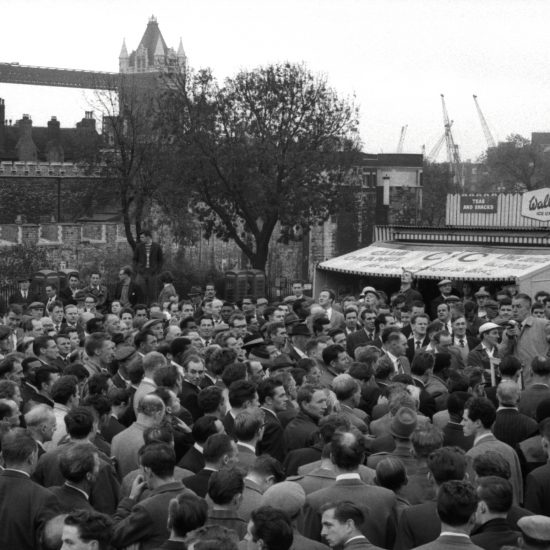 A Union meeting by the Tower of London, with Tower Bridge in the background,  in 1961, including union members listening to a man speaking through a microphone