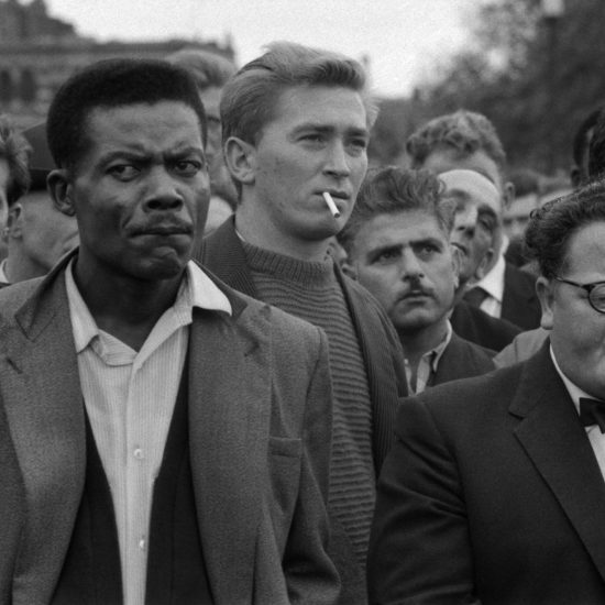 A close-up of male trades union members listening to a speaker at a meeting by the Tower of London in 1961
