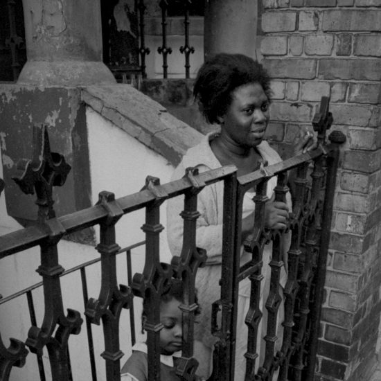 A woman and her daughter look at the street from behind the railings of a basement flat in Notting hill, West London, as a civil rights demonstration passes out of shot, circa 1963