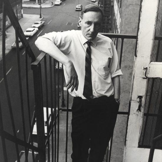 American Beat author William S Burroughs stands on a fire escape in New York City in 1965, with the street in the background