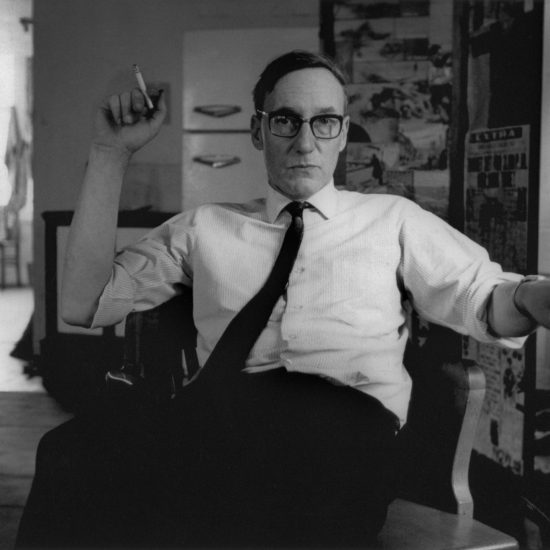 American Beat author William S. Burroughs is seated in an apartment in New York City in July 1965, smoking and gesturing with his left hand