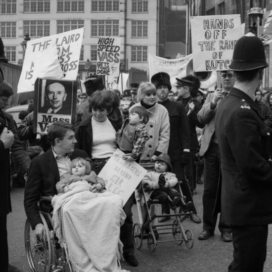 """On 01 May 1965 (May Day), Private Eye magazine holds a """"Mass for Vass"""" rally in Central London for former British Prime Minister Alec Douglas-Home, a reference to his nickname """"Baillie Vass"""". Peter Cook in a wheelchair pushed by John Wells fronts 300 marchers carrying banners, including Richard Ingrams carrying one proclaiming 'Hands off the Rann of Kutch!'"""