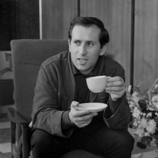 British author, dramatist and poet Arnold Wesker drinks tea whilst being interviewed by an unseen male. He leans forward in his chair and looks off-camera, circa 1962