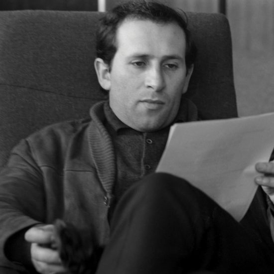 British author, dramatist and poet Arnold Wesker sits and studies paperwork: he also holds a cigarette, England, circa 1962