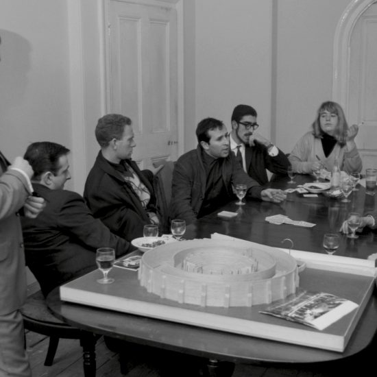 Arnold Wesker (4th from left), Benny Green, unknown musicians and others at a meeting with an architect's model of the Camden Roundhouse on the table, circa 1963