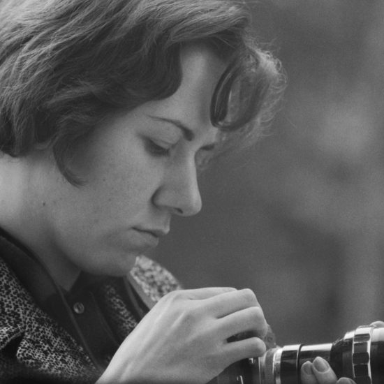 Photographer and journalist on the jazz scene Val Wilmer looks at and holds a 35mm camera, circa 1965