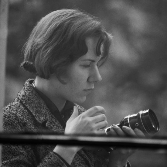 Photographer and journalist on the jazz scene Val Wilmer looks at and holds a 35mm camera, seen through a closed window, circa 1965