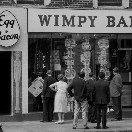 An exterior shot of passers-by looking at a modern sculpture in the window of a Wimpy Bar in London, circa 1961