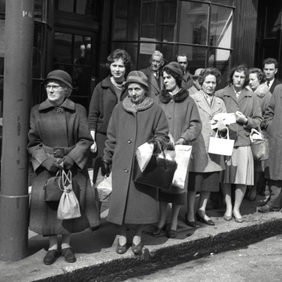 A crowd of people in winter coats queue on a sunny pavement outside a shop in London, February 1960