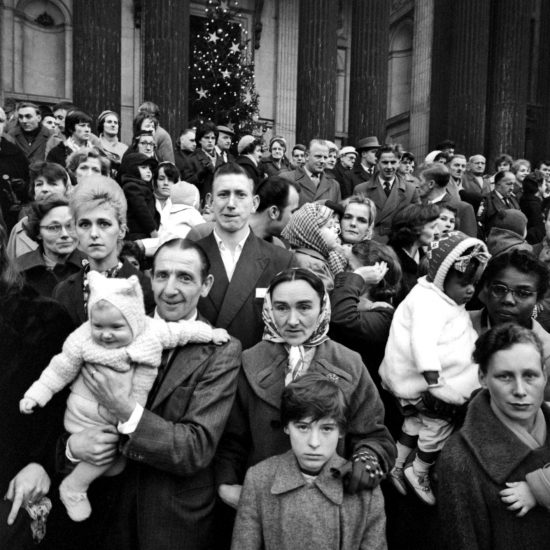 A large crowd of people, including babies, gathers in front of a Christmas tree during a demonstration against homelessness held on Oxford Street, London, during December 1961