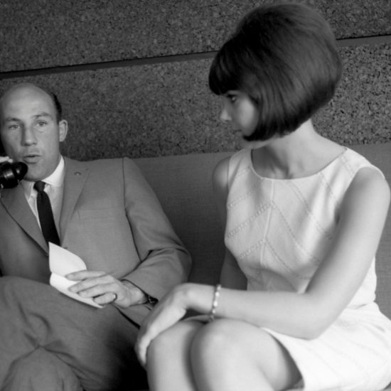 In 1964 English racing driver Stirling Moss and his American wife Elaine Barberino sit on a sofa together - Stirling speaks on a telephone whilst Elaine looks at him. Elaine has a perfect beehive hairstyle and they are both dressed fashionably
