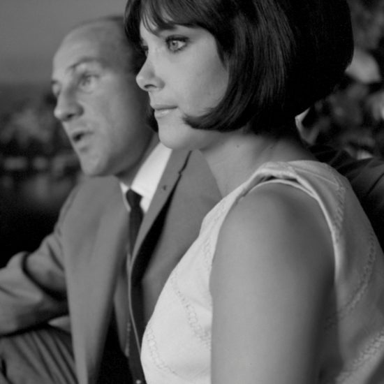 In 1964 Stirling Moss and and his wife Elaine Barberino look off camera, with Stirling in the background and Elaine in the foreground. Elaine has a perfect beehive hairstyle and they are both dressed fashionably